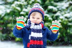 Cute little funny kid boy in colorful winter fashion clothes having fun and playing with snow, outdoors during snowfall. Cute little funny child in colorful Royalty Free Stock Image