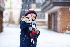 Cute little funny kid boy in colorful winter fashion clothes having fun and playing with snow, outdoors during snowfall. Cute little funny child in colorful Royalty Free Stock Photos