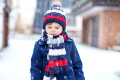 Cute little funny kid boy in colorful winter fashion clothes having fun and playing with snow, outdoors during snowfall. Cute little funny child in colorful Royalty Free Stock Photo