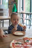 Cute little 2 years girl eating pizza in the restaurant stock photos