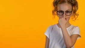 Cute little genius adjusting eyeglasses and looking into camera, education