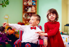 Cute little gentleman in wheelchair and lady on holidays in kindergarten for kids with special needs Royalty Free Stock Images