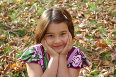 Cute little girl. Sitting on grass Royalty Free Stock Photos
