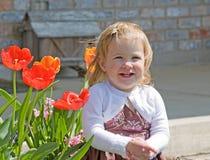 Cute Little Girl. Little Girl Sitting Outside Enjoying Flowers Royalty Free Stock Photo