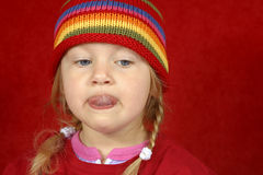 Cute Little Girl. A cute little girl with a red and multi color-striped hat making silly faces Royalty Free Stock Images