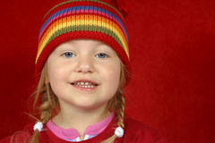 Cute Little Girl. A cute little girl with a red and multi color-striped hat on a red background Stock Photos