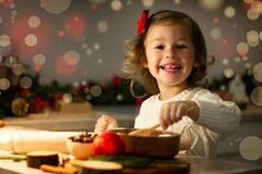 Free Cute Little Girl 2-4 With A Red Bow Prepares Christmas Gingerbread Cookies In The New Year`s Kitchen Royalty Free Stock Photo - 197521975