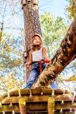 Cute little girl in the Adventure Park. Little girl is climbing in the adventure park stock photography
