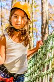 Cute little girl in Adventure Park. Little girl is climbing in the adventure park Stock Photo