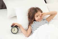 Cute little girl with alarm clock awaking in bed. Healthy sleep stock image
