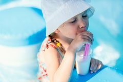 All inclusive vacation. Cute little girl at all inclusive resort swimming pool sipping cocktail Stock Image