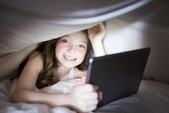 Cute little girl alone with tablet computer under blanket at night in a dark room Royalty Free Stock Photography