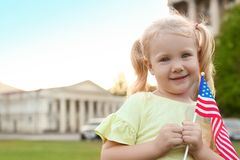 Cute little girl with American flag. On city street. Space for text stock photo