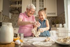 Free Cute Little Girl And Her Grandmother Cooking On Kitchen. Stock Images - 160620254