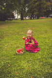 Cute little girl with apples in a green grass. Royalty Free Stock Images