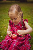 Cute little girl with apples in a green grass. Stock Photo