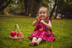 Cute little girl with apples in a green grass. Stock Images