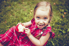 Cute little girl with apples in a green grass. Royalty Free Stock Photography