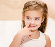 Cute little girl  applying cream Stock Images