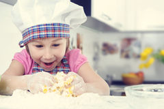 Cute little girl in apron baking cookies Royalty Free Stock Photos