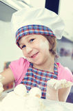 Cute little girl in apron baking cookies Royalty Free Stock Images