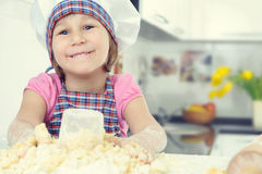 Cute little girl in apron baking cookies Stock Image