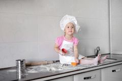 Cute little girl in apron and chef hat is kneading the dough and smiling while baking.  Royalty Free Stock Image
