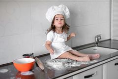 Cute little girl in apron and chef hat is kneading the dough and smiling while baking.  Stock Images