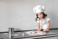 Cute little girl in apron and chef hat is kneading the dough and smiling while baking.  Stock Photo