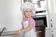 Cute little girl in apron and chef hat is kneading the dough and smiling while baking.  Royalty Free Stock Photos