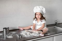 Cute little girl in apron and chef hat is kneading the dough and smiling while baking.  Stock Image