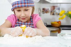 Cute little girl in apron cooking cookies Stock Photos