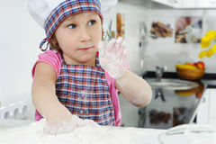 Cute little girl in apron cooking cookies Stock Images