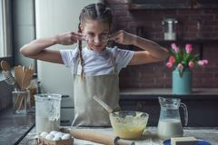 Little girl baking. Cute little girl in apron is making lines on her face with flour ready to cook, in kitchen at home Stock Photo