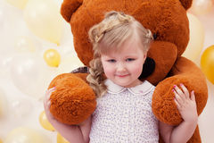Cute little girl in arms of large teddy bear Royalty Free Stock Photo