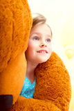 Cute little girl in arms of teddy bear, close-up Stock Photography