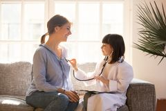 Cute girl as doctor playing with happy mom pretending nurse. Cute little girl as doctor playing with happy mom pretending nurse, playful kid daughter dressed as stock photos