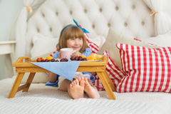 Free Cute Little Girl At Breakfast On A Bed - A Focus On A Legs Stock Images - 75617604