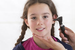 Cute little girl attending a medical check-up. Doctor Examining Child's Ears In Doctor's Office Royalty Free Stock Photos