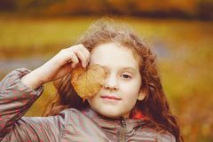 Cute little girl with autumn leaves stock images