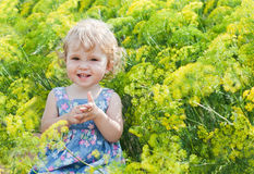 Cute little girl on the background color of dill. Cute little girl on a background of flowers of dill on a summer day stock photography