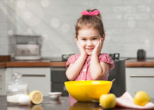 Cute little girl baker on kitchen with baking ingredients Stock Photo