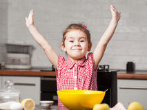 Cute little girl baker on kitchen with baking ingredients Royalty Free Stock Photo