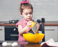 Cute little girl baker on kitchen with baking ingredients Royalty Free Stock Photos