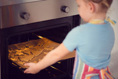Cute little girl baking Christmas cookies in oven Royalty Free Stock Images