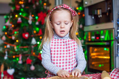 Cute little girl baking gingerbread cookies for Stock Images