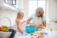 Cute little girl baking with her grandmother Stock Photos