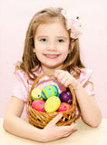 Cute little girl with basket full of colorful easter eggs Stock Image