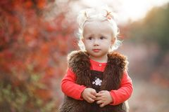 Cute little girl with a basket of red apples in the fall in the park royalty free stock photos