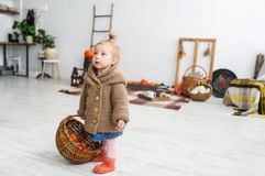 Cute little girl with a basket is in white big room. Stock Photography